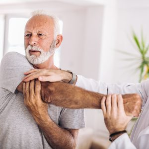 Man having chiropractic arm adjustment. Physiotherapy, sport injury rehabilitation. Senior man exercises in center for chiropractic.