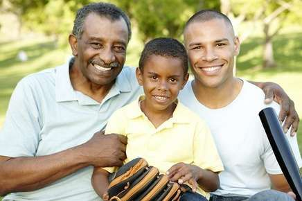 Image of a grandfather, son and grandson with baseball bat and glove.