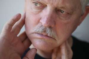image of man in pain pressing his fingers against his jaw
