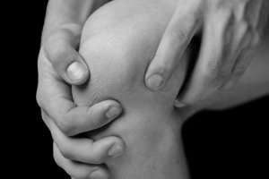 close up image of two hands holding a knee in pain