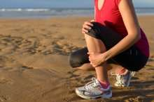 image of a woman gripping her shin