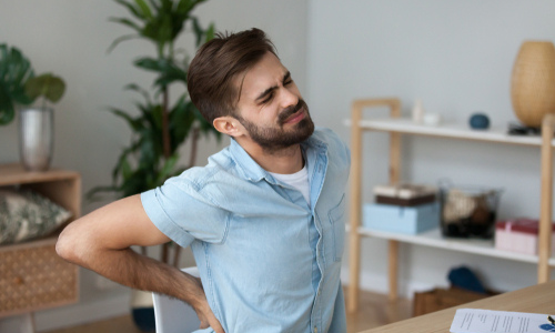 Man in pain at a desk from herniated disc