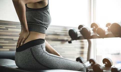 Woman experiencing back pain while exercising