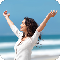 image of woman on the beach raising her arms